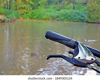 Fragment of steering wheel of bicycle with grips, shifters and brake lever against  background of  blur lake in  fall in forest or park