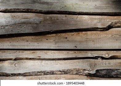 Fragment of a sturdy wooden fence. Horizontal boards are nailed tightly to each other. Wooden background. Blur,