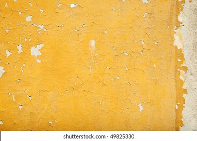 Fragment of tumbledown yellow painted stone wall