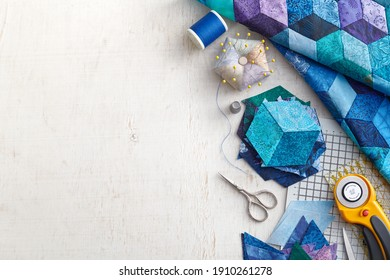 Fragment of tumbling blocks quilt, accessories for quilting on a white surface. Space for text.