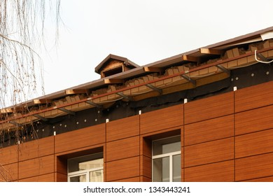fragment of unfinished roof, building exterior. repair of the roof of a new brown residential building on the white sky background