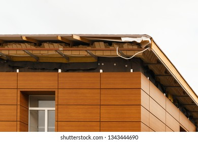 fragment of unfinished roof, building exterior. repair of the roof of a new brown residential building on the white sky background. roof in repair