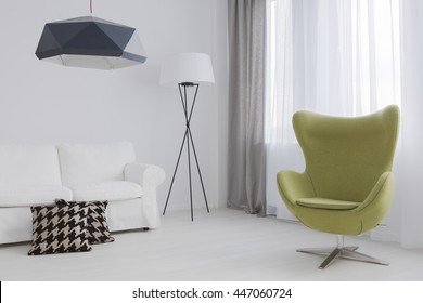 Fragment of a very bright lounge room with a green egg chair and a comfy sofa