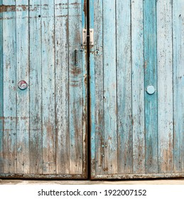 fragment of very old wooden door with blue cracked paint, parallel boards, full frame
