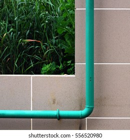 A fragment of a wall with a pipe and a grass on the background. Russia, town of Puschino, July 2014.