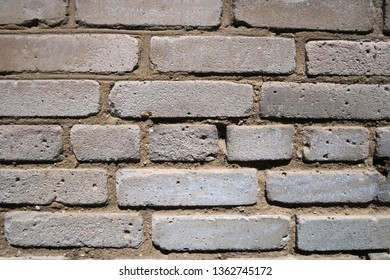 Fragment of weathered wall of old building made of grey bricks. Abstract texture background