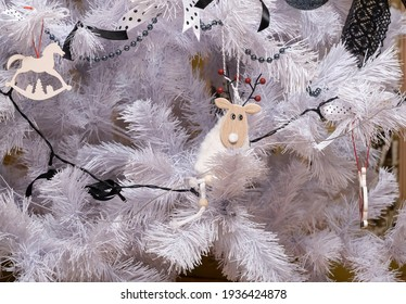 Fragment of a white artificial Christmas tree with different New Year decorations. Horizontal aspect ratio.