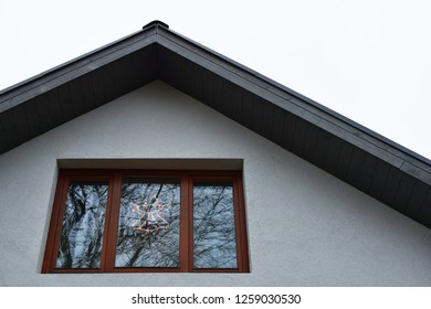 Fragment of white house with wooden eaves and brown window with christmas lights in shape of angel as xmas decoration and reflections of tree on glass with copy space on facade or sky in evening.