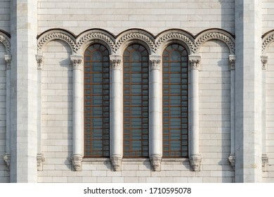 Fragment of the white marble facade of a building in the Byzantian style with a triple arched window and columns