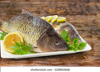 Fragment of the white square dish with two different carps with peeled scales and prepared for cooking, lemon slices and parsley twigs closeup on a rustic wooden table at selective socus