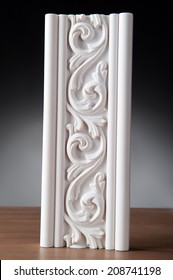 Fragment of white stucco molding, elements of decoration on wooden desk, closeup over dark background