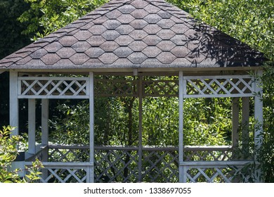 Fragment of white wooden summerhouse surrounded by lush green trees on bright sunny summer day