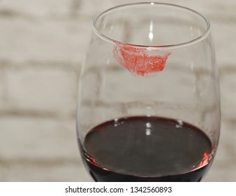 A fragment of a wine glass with lipstick marks.