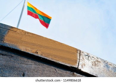 Fragment of wooden ship in Nida resort town near Klaipeda in Neringa on the Baltic Sea at the Curonian Spit in Lithuania. Lithuanian flag