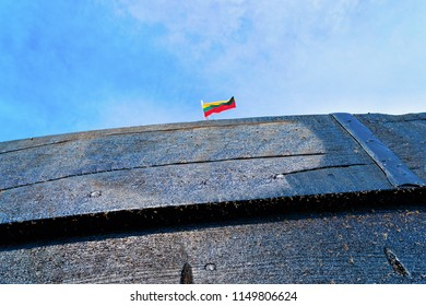 Fragment of wooden ship at Nida resort town near Klaipeda in Neringa on the Baltic Sea at the Curonian Spit in Lithuania. Lithuanian flag