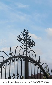 Fragment of wrought iron fence ornament. Artistic ornament forging. Cross decorated with swirls and flowing lines against blue sky