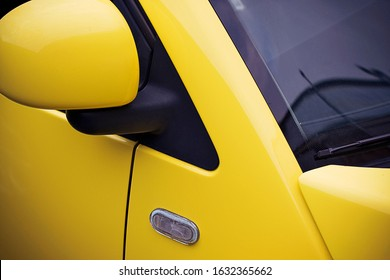 Fragment of a yellow car with a side view mirror, a windshield and a side direction indicator.