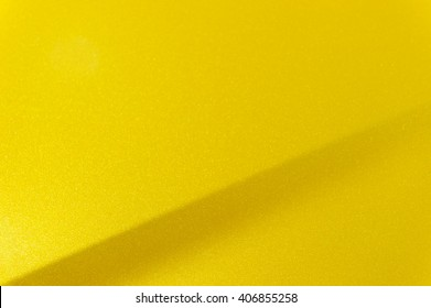 Fragment of yellow steel car bodywork, vehicle silver paint coating texture, selective focus, abstract