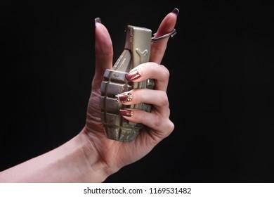 fragmentation grenade in woman hand on black background