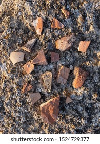 Fragments of ancient ceramic pottery on sea shore top view texture background