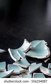 Fragments of a broken light blue vase on a black surface, detail