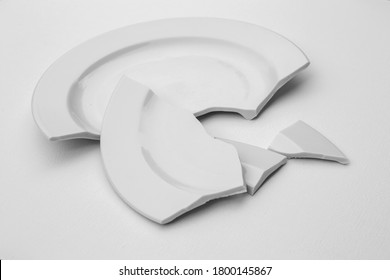 fragments of a broken plate on a light background, black and white photo. The concept of breaking up relations, divorce, destruction
