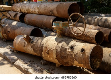Fragments of old large water pipes. After many years of operation, destroyed metal pipe was destroyed. Vegetable steel tube with hole corrosion. Rusty metal pipe. Selective focus