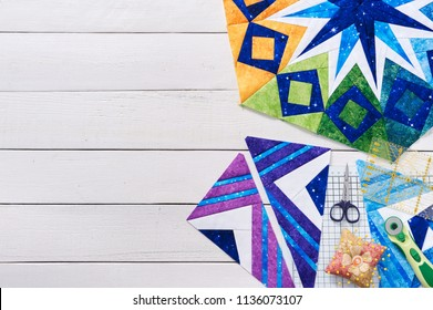 Fragments of quilt, accessories for patchwork, top view on a white wooden surface with a copy space