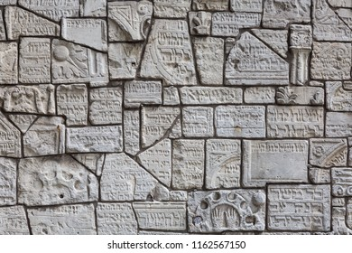 Fragments of ruined jewish tombstones on a wall in the jewish cemetery in Krakow