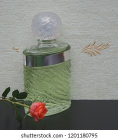 fragrance for ladies, large perfume bottle in front of the satin wallcovering Elysee decorated with an English rose
