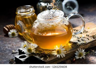 fragrant chamomile tea in a glass teapot, closeup, horizontal