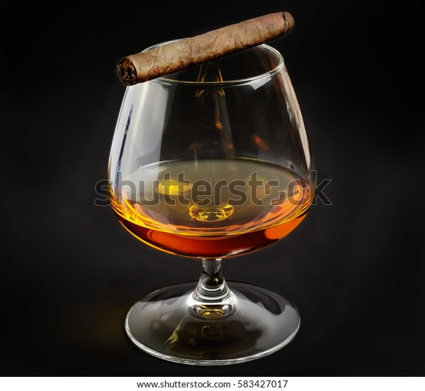 Fragrant cigar on glass with whiskey.