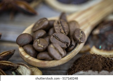 fragrant coffee beans in a beautiful wooden spoon on wooden background