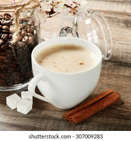 Fragrant coffee on a wooden table. Next to a cup of coffee cinnamon, three lumps of sugar, a jar of coffee beans and sprigs of flowering apricots
