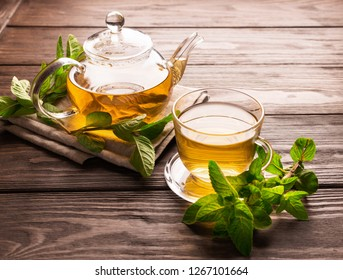 Fragrant fresh herbal tea of ​​mint and melissa in a glass cup and a teapot on a dark wooden background. Traditional herbal drink. Place for text or design.