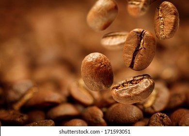 Fragrant fried coffee beans with focus on one are falling