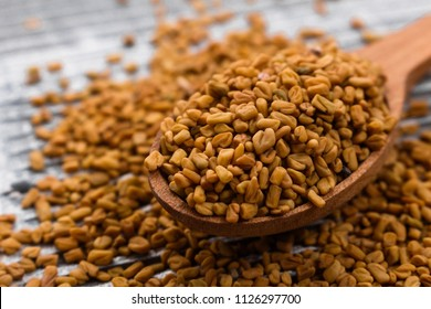 fragrant grains of fenugreek on a rustic background