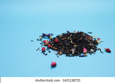 Fragrant herbal dry leaf tea with fruits and petals on blue background