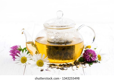 fragrant herbal tea in a glass teapot on white background, horizontal