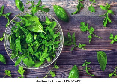 fragrant herbs: basil, arugula, parsley on the table. washed fresh parsley, arugula, basil leaves in a colander. view from above.