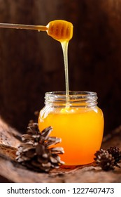 Fragrant honey flowing from a stick into a glass jar against the background of tree bark and cones. Close-up.