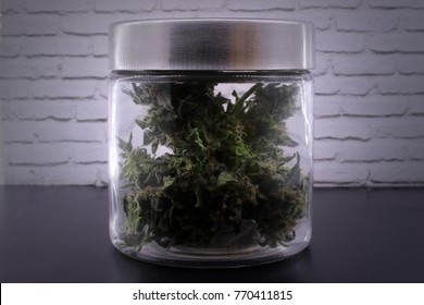 Fragrant marijuana buds in glass jar on a black table and with a white background