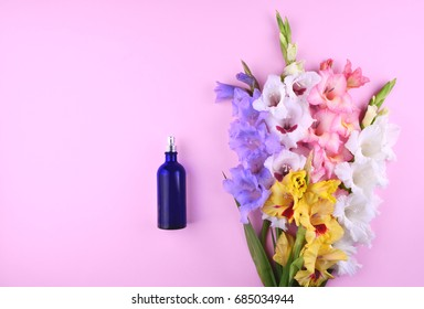 Fragrant perfume with beautiful gladiolus flowers on pink trendy background. Place for your text.