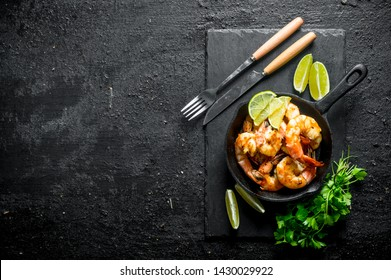 Fragrant shrimps on a stone Board with parsley and lime. On black rustic background