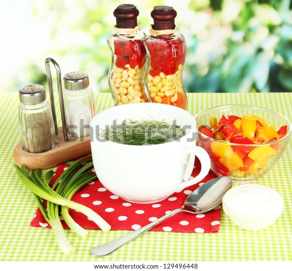 Fragrant soup in cup on table in garden