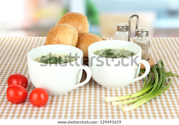 Fragrant soup in cups on table in kitchen