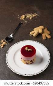 Framboisier cake made with fresh raspberries and roasted pistachio sitting on a white plate. Two gingerbread men biscuits, a silver spoon and some crumbs are sitting on a grey surface.