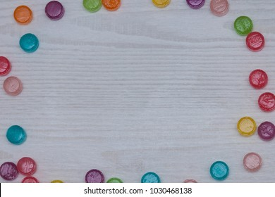 Frame with assorted colored candies on wodden white table. Flat lay, top view