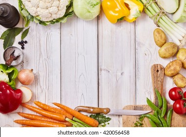Frame of assorted healthy fresh farm vegetables, a cutting board, knife, salt and pepper mill on a white wooden background with central copy space, overhead view