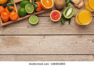 Frame with assortment of citruses on rustic wooden background, copy space. Top view on oranges, lemons, tangerines and other exotic fruits, flat lay